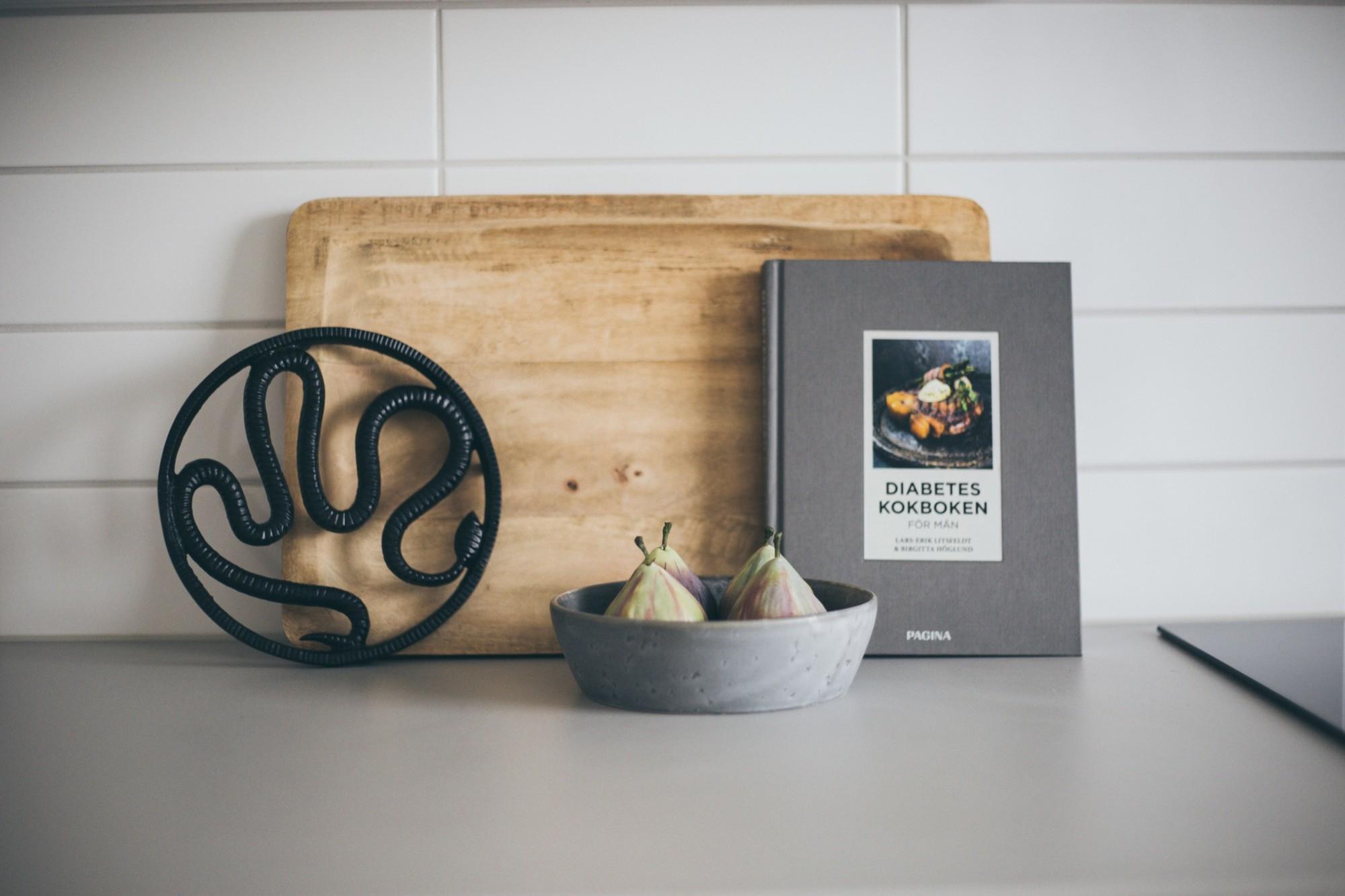 skärbräda i trä lutad mot vägg och grå skål med fikon