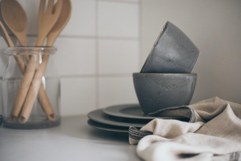 gråblå koppar och fat på en köksbänk