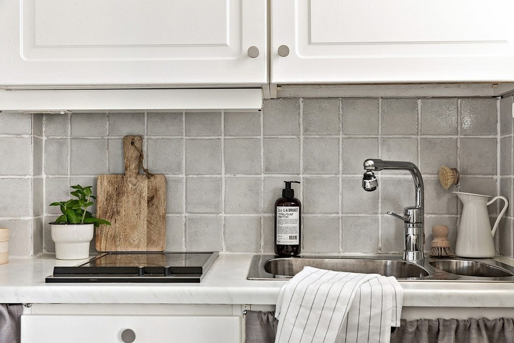 köksbänk med ljusgrått kakel och vita skåpsluckor