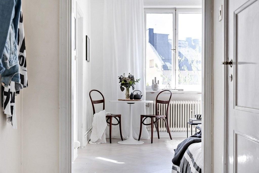 vardagsrum med vitt bord och bruna böjträstolar