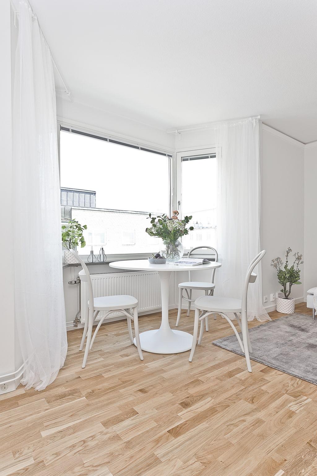 ljus vardagsrum med vitt matbord vid burspråket