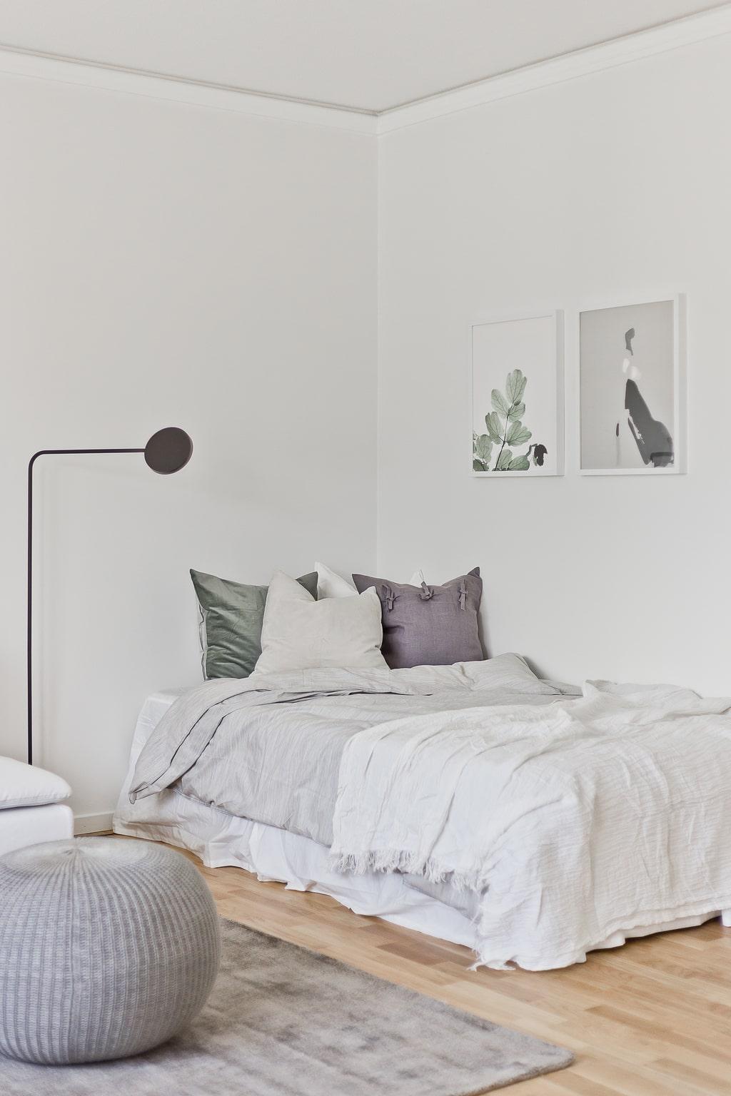 ljust sovrum med bäddad säng, ljusa tavlor, svart golvlampa och grå sittpuff