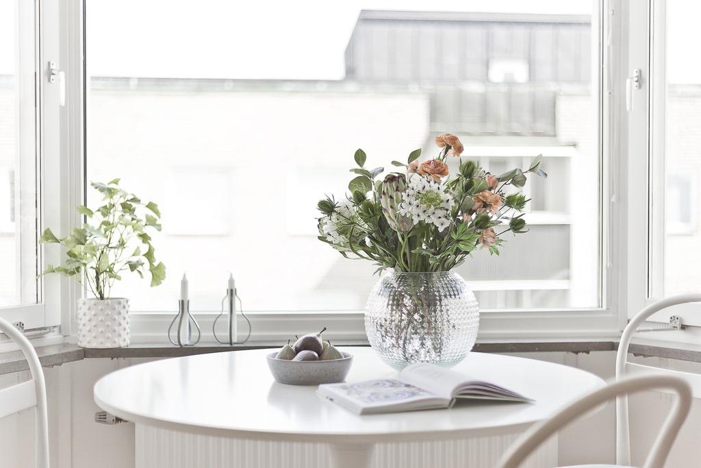 vitt matbord med rund skiva framför burspråk och en vas med blommor på bordet