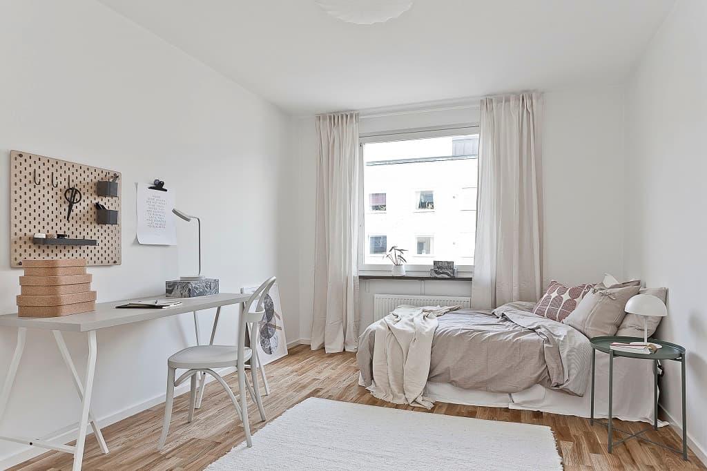 ljust sovrum med säng, matta och ett litet skrivbord