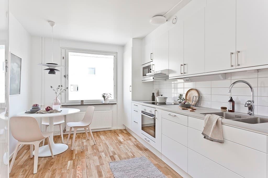 ljust kök med vita luckor och vita möbler
