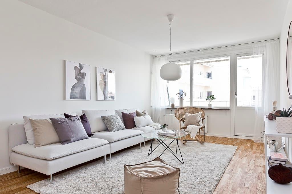vardagsrum med soffa fylld med kuddar