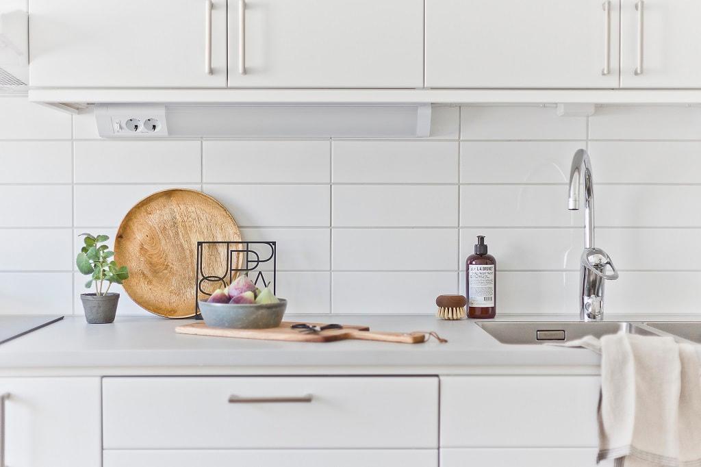 detaljbild på köksbänk med vitt kakel i nakgrunden