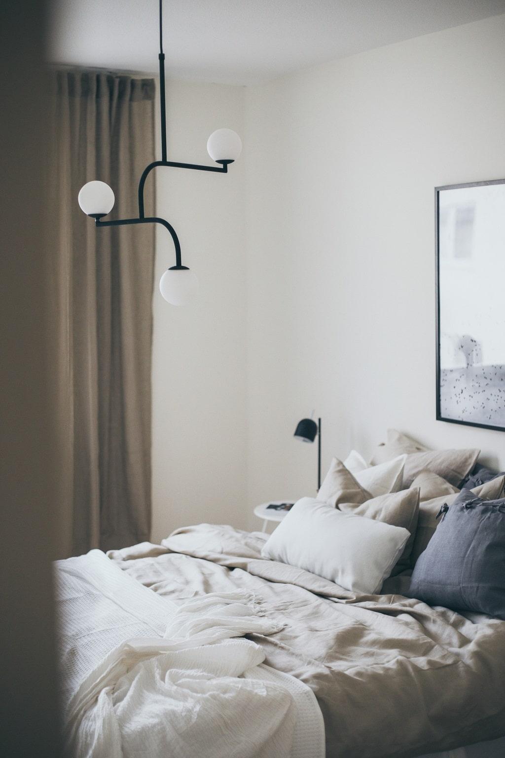 Sovrum med säng bäddad med begia färger