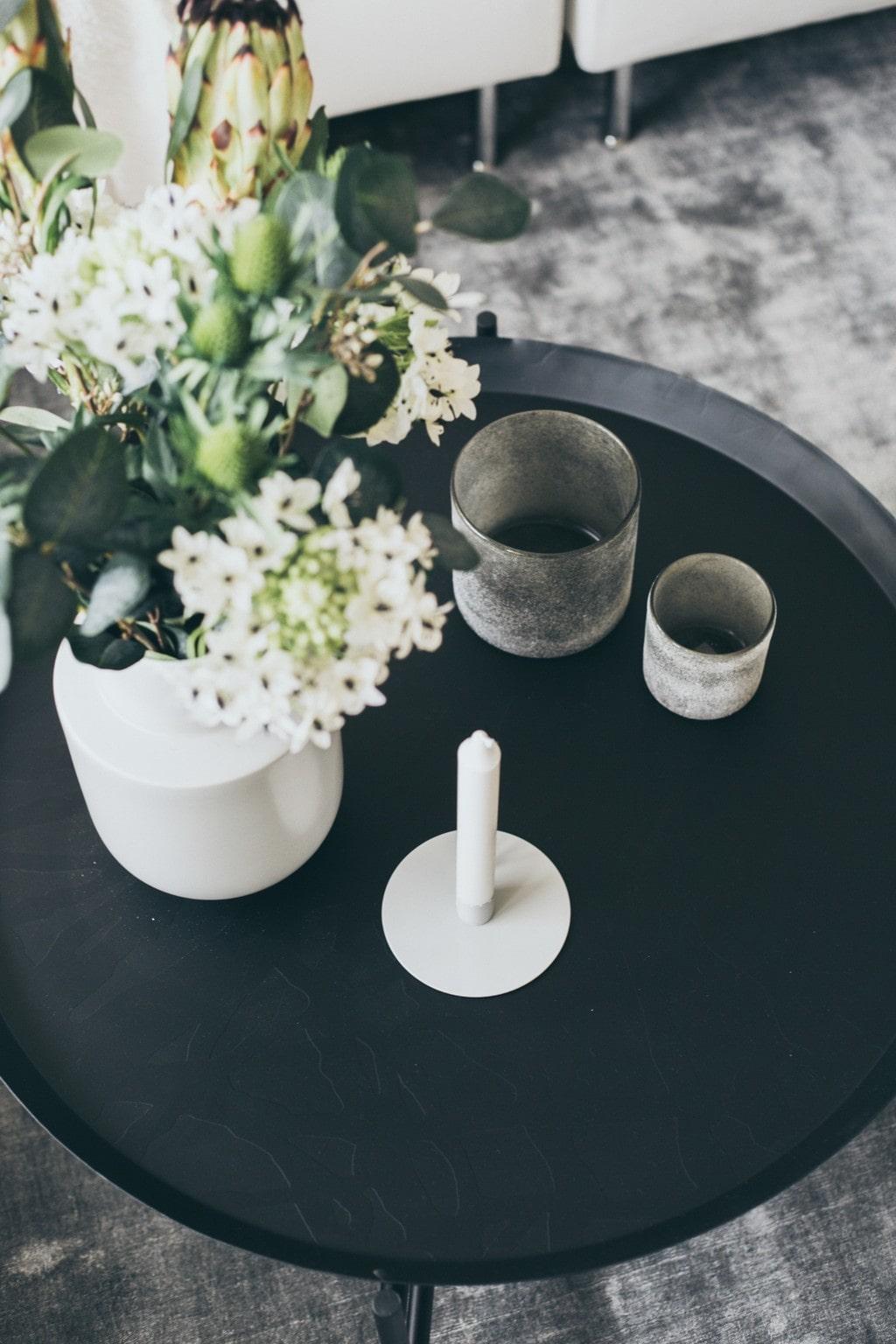svart sidobord med två ljuslyktor och blommor i vit vas