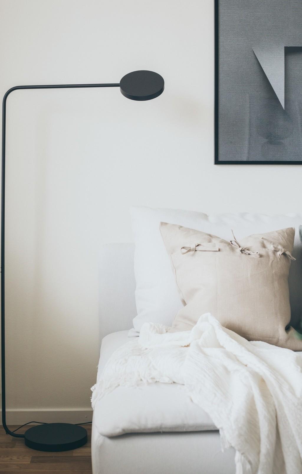 beige soffa med ljusa kuddar och svart golvlampa