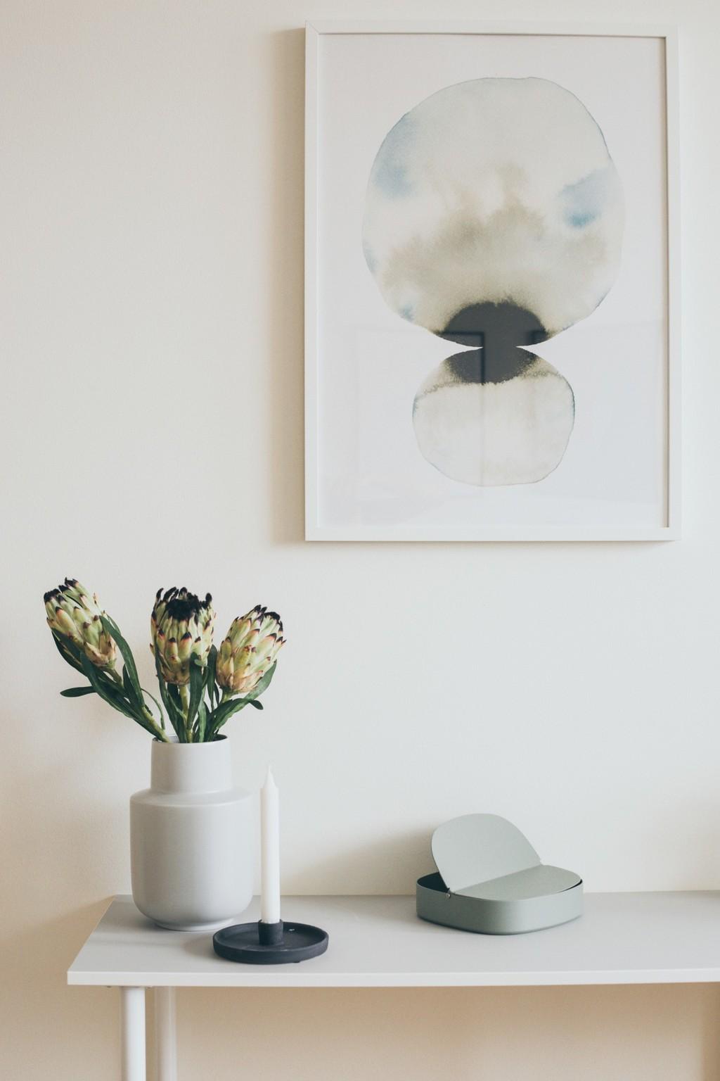 vitt sideboard med vit vas och ljusgrön ask