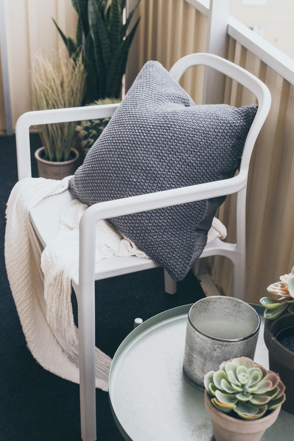 vit stol och ljusgrönt sidobord på en balkong