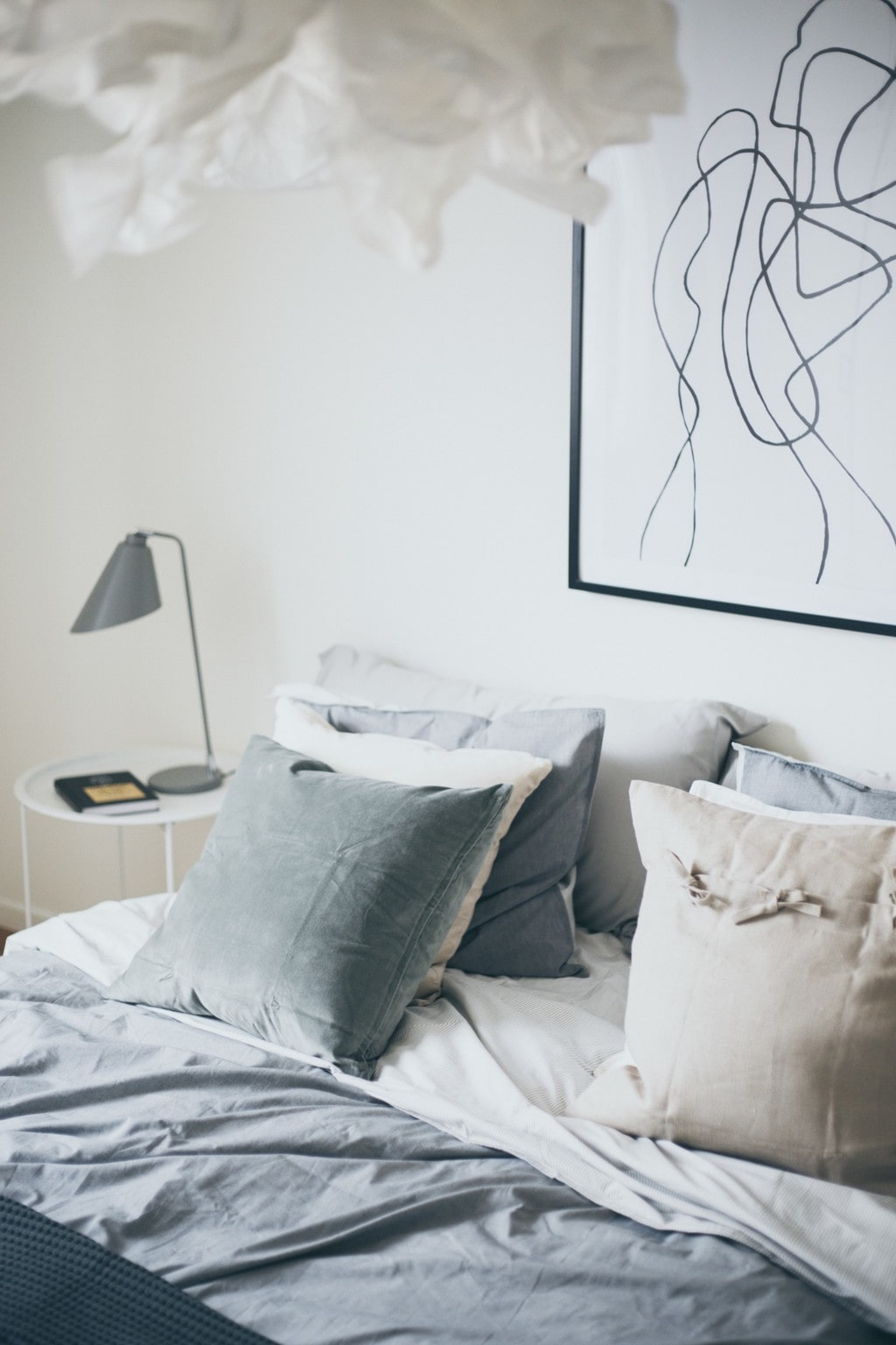 bäddad säng med flera kuddar i ljusa färger