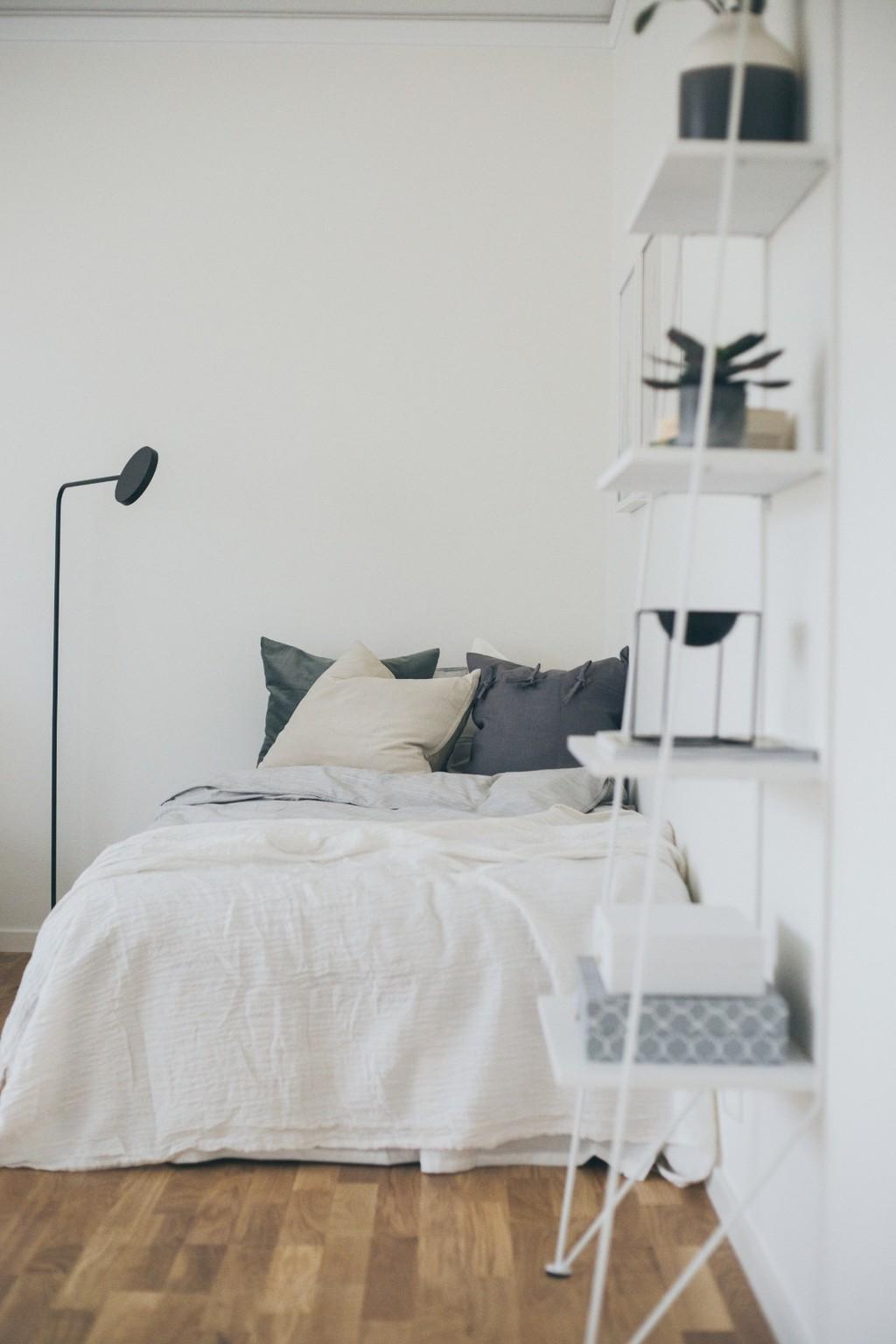 bäddad säng med beige, grön och grå kuddar, vit bokfylla som lutar mot väggen och en svart golvlampa