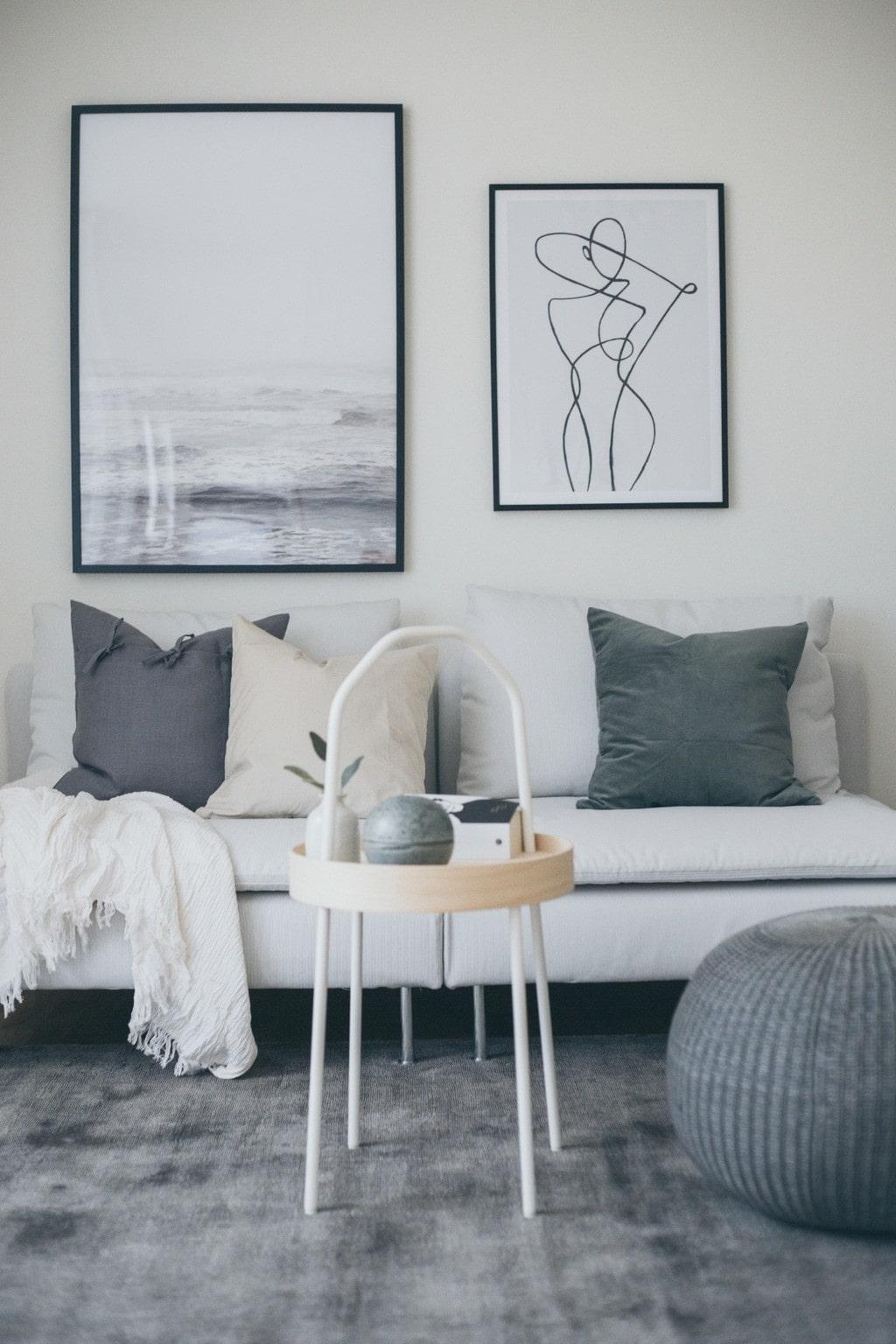 ljus soffa med beige, grön och grå kuddar, soffbord med skiva i trä och en sittpuff