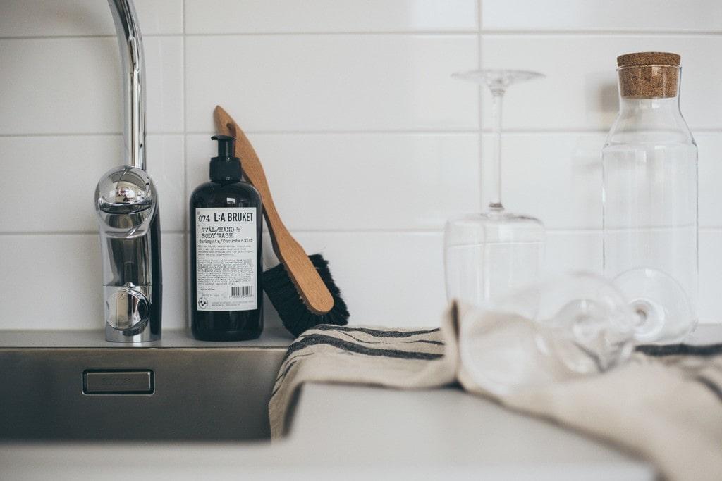 närbild på köksbänk med diskborste i trä och rena vinglas