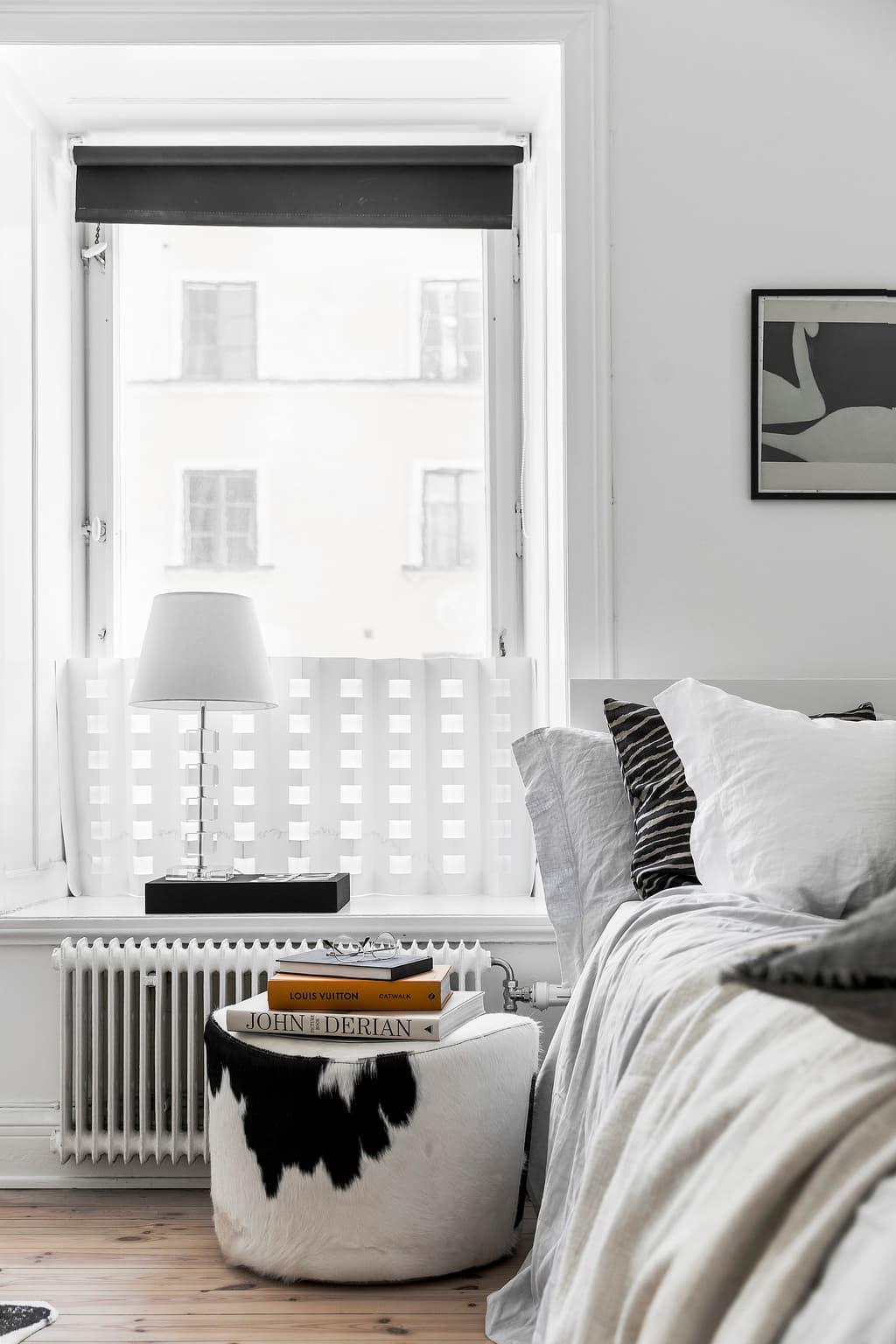 bäddad säng med koskinnspuff bredvid