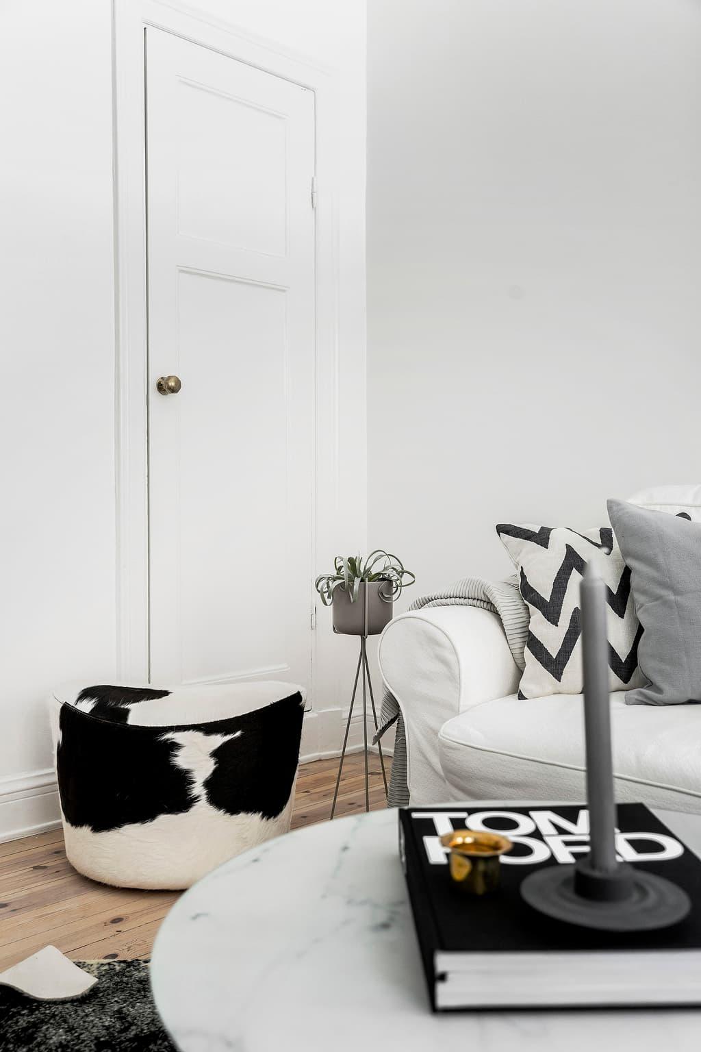 puff i koskinn och vit soffa