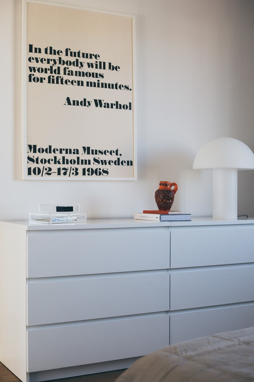 vita byråer med böcker, lampa och tavla ovanför