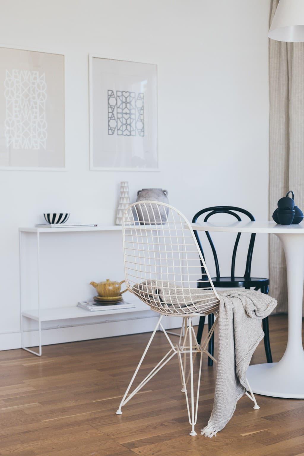 vitt matbord med stolar runt och ett sideboard i bakgrunden