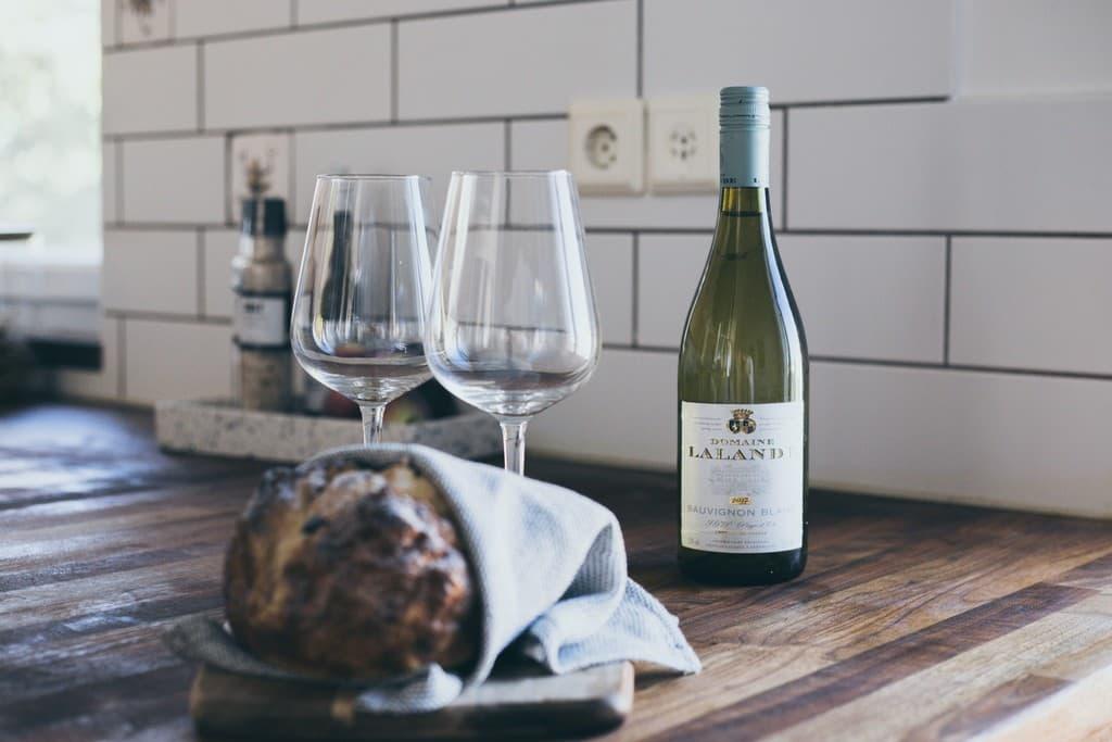 mörk bänkskiva med brödlimpa, vin och vinglas