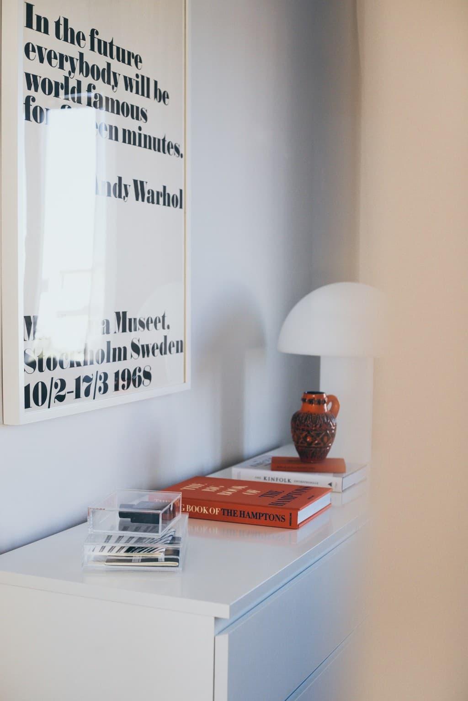 vit byrå med böcker, lampa och tavla ovanför