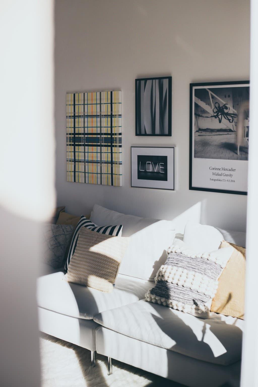 soffa med kuddar och tavlor bakom