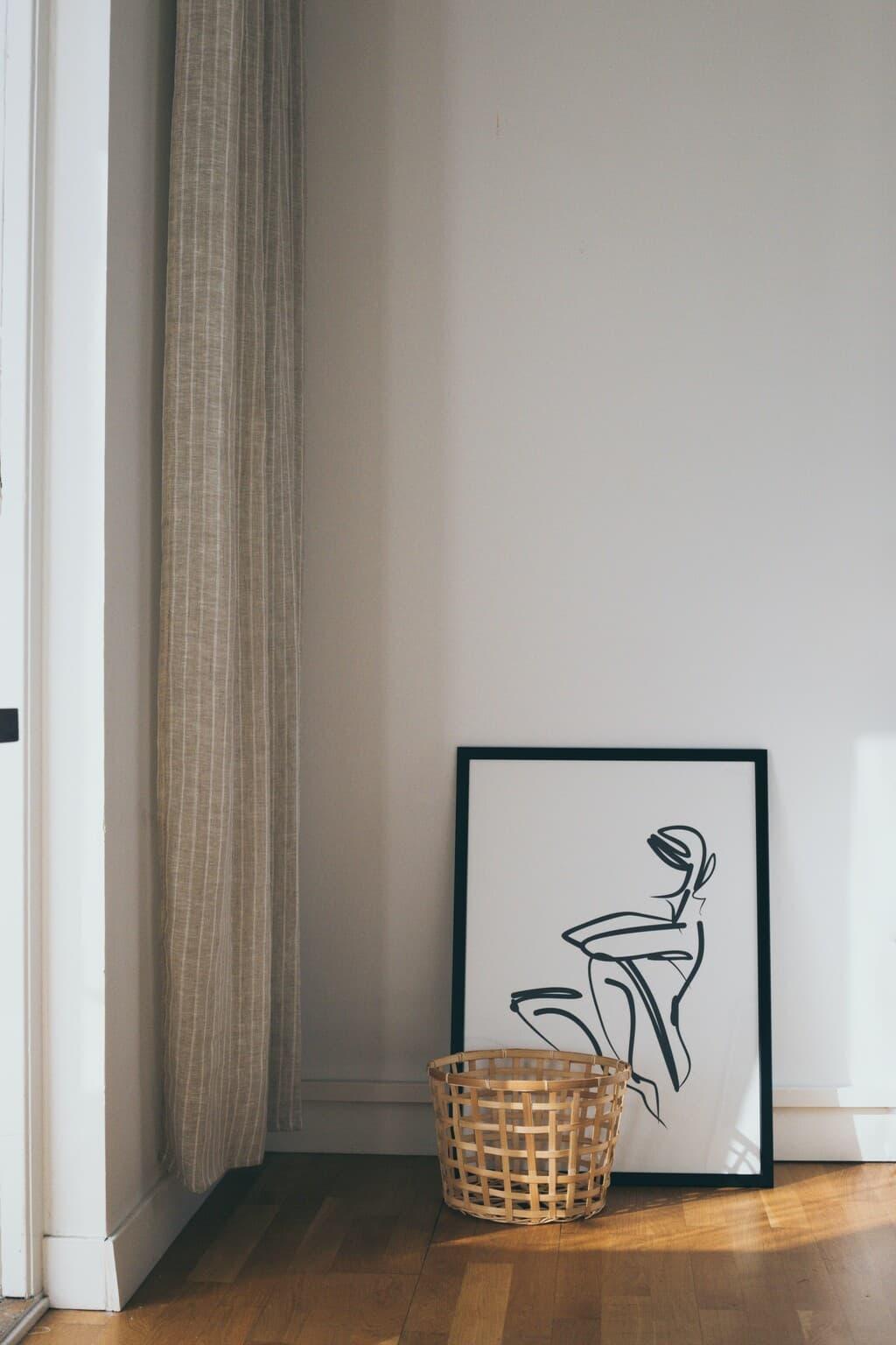 vägg med tavla och korg på golvet