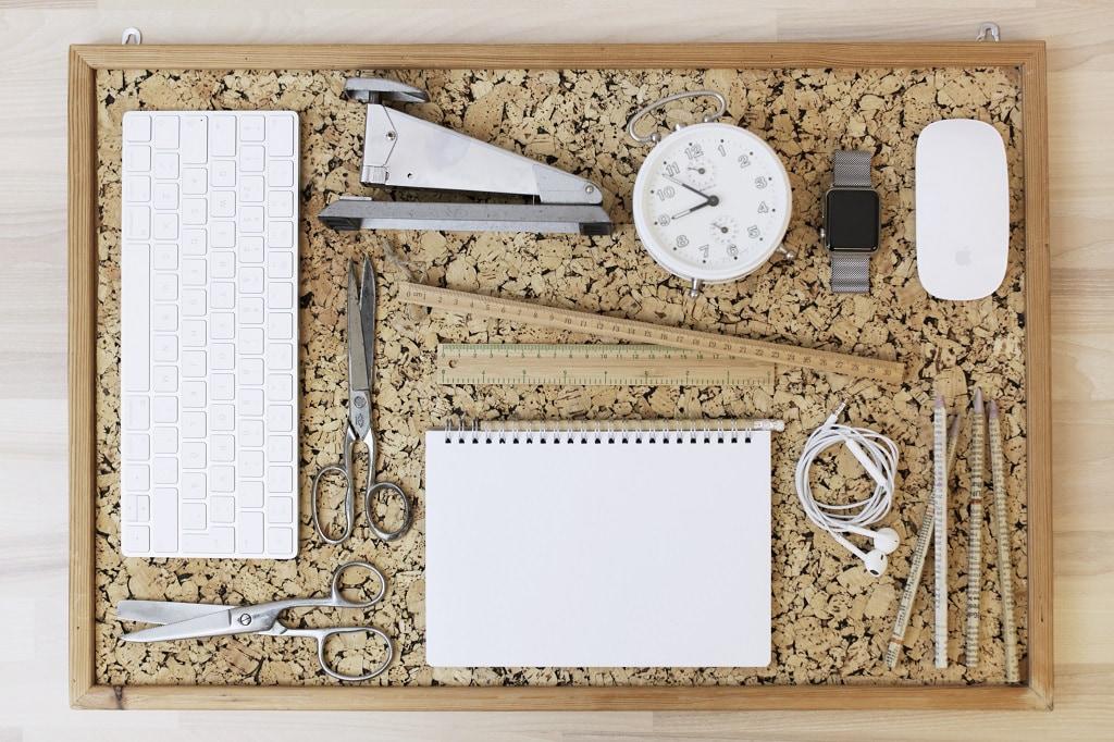 ansalgstavla med tangentbord, häftapparat, väckarklocka, linjaler, saxat, block, hörlurar, pennor och mus