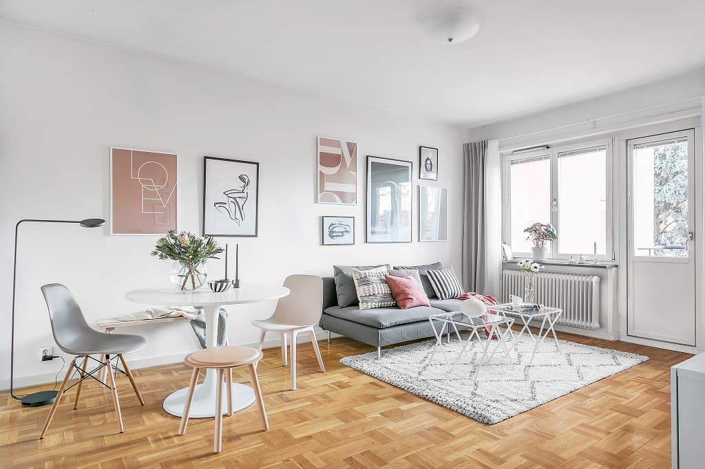vardagsrum med pelarbord och stolar till vänster och soffa med soffbord till höger