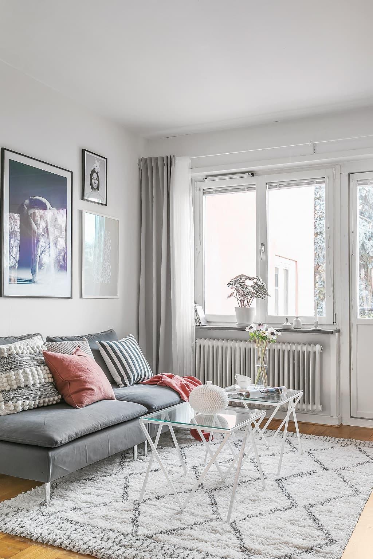 vardagsrum med grå soffa, två glasbord och en matta