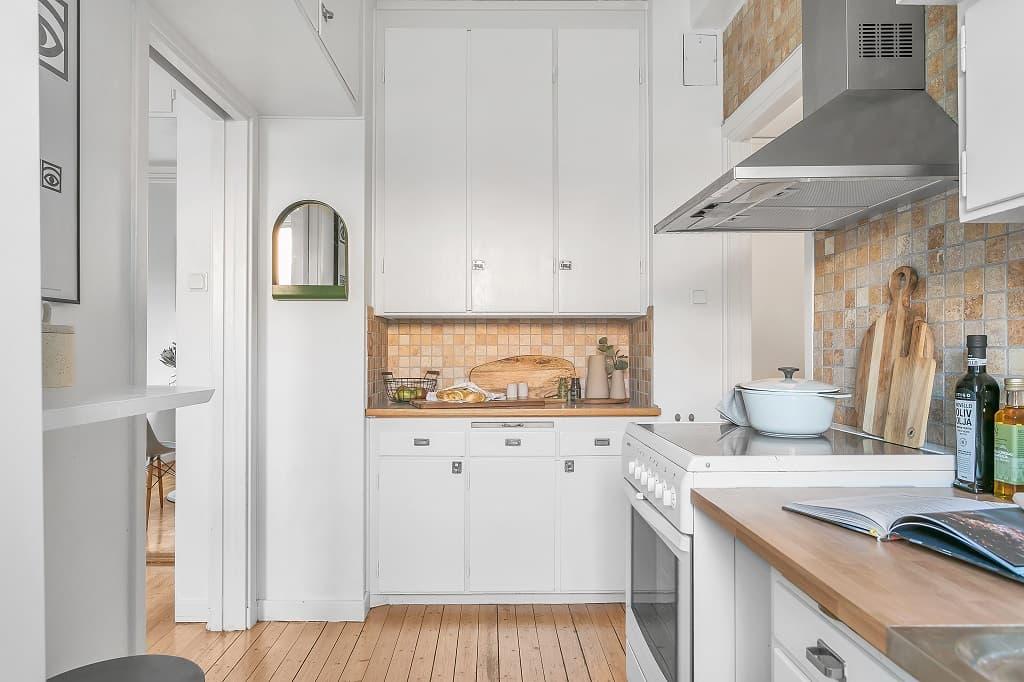kök med vit inredning, trägolv och brunt kakel