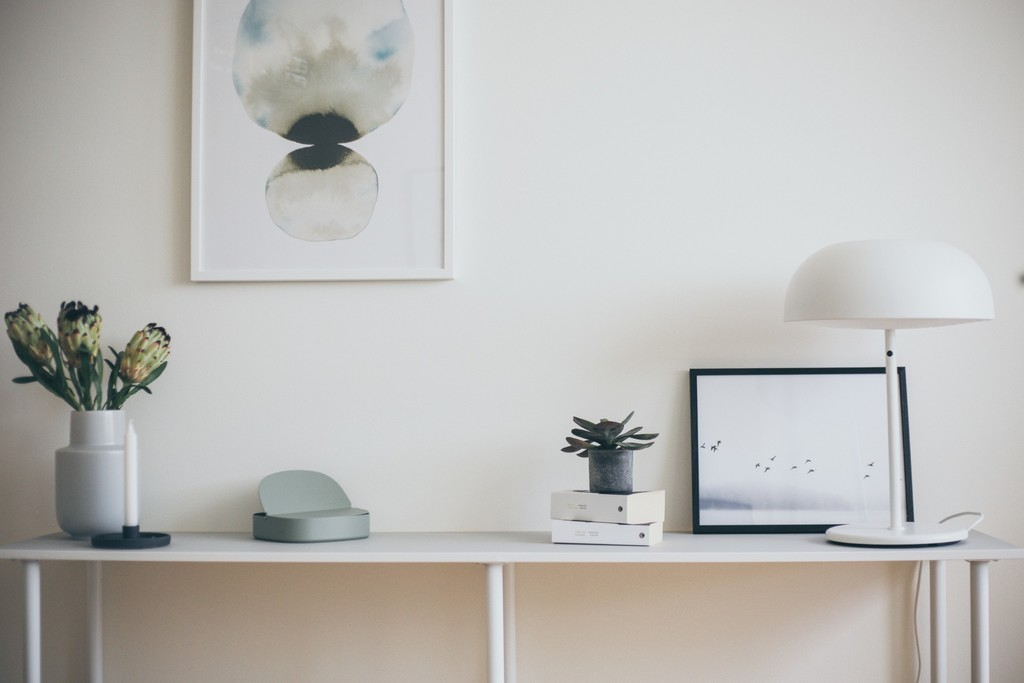 vitt sideboard med lampa och tavlor