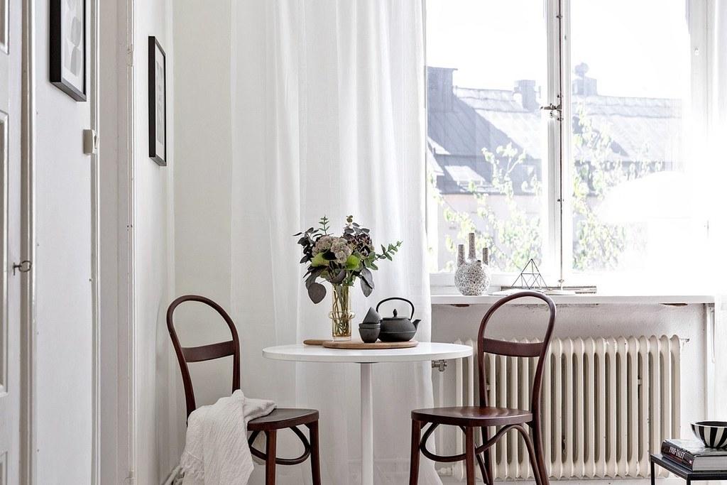 runt bord med bruna böjträstolar i vardagsrum