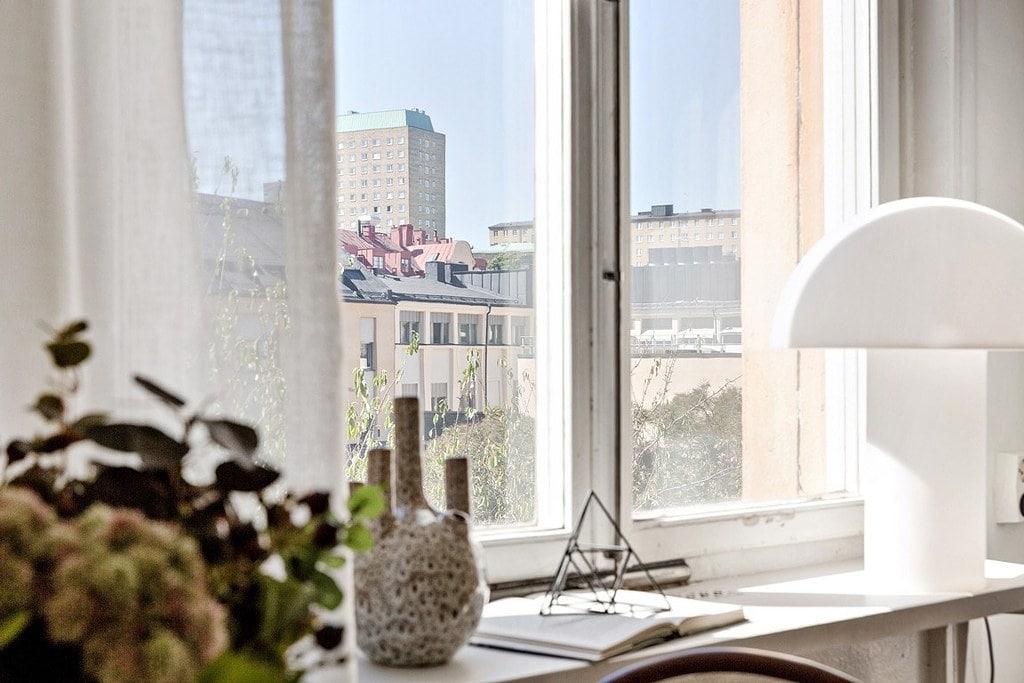 fönsterbräda med vit lampa och vas med utsikt över fasader