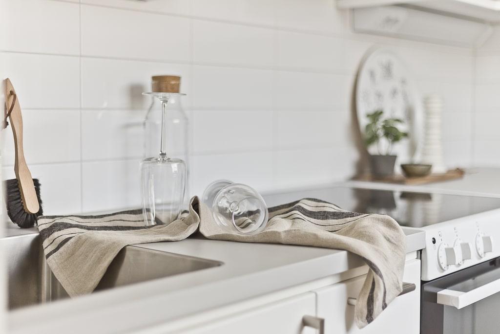 närbild på köksbänk med diskade vinglas och en spis i bakgrunden
