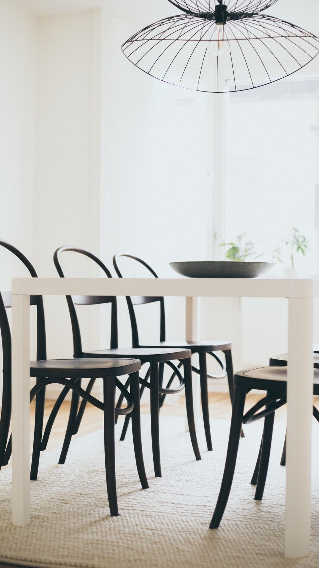 detaljbild på ljust bord i matsal med stolar i mörkt böjträ i bakgrunden