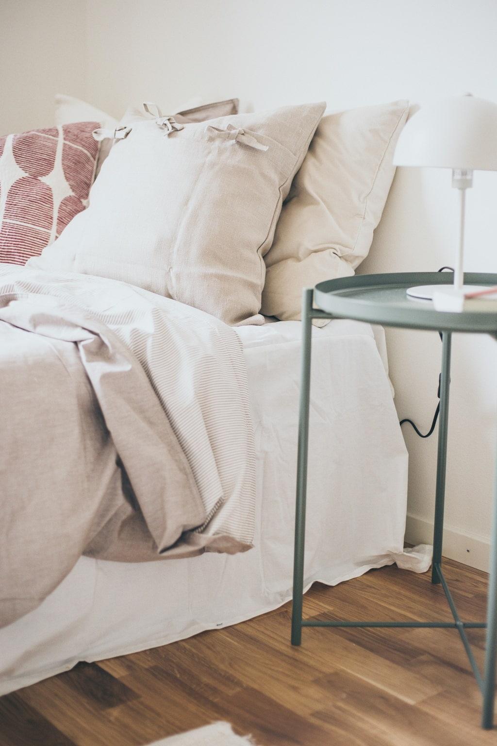 Detaljbild på bäddad säng och ljusgrönt sängbord