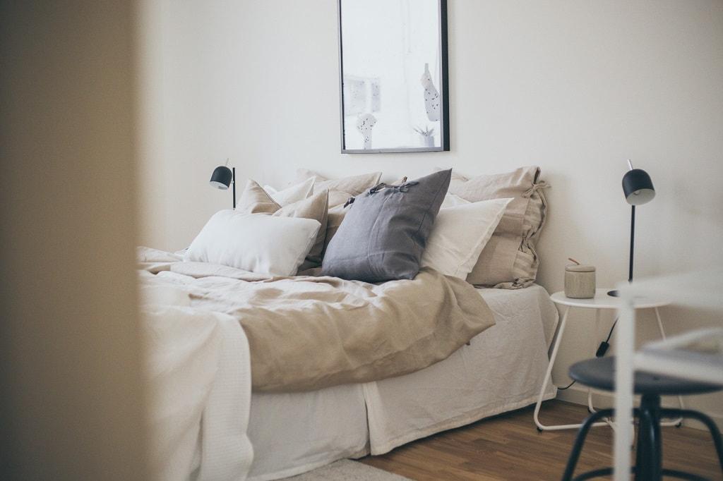 Bäddad säng med överkast och prydnadskuddar