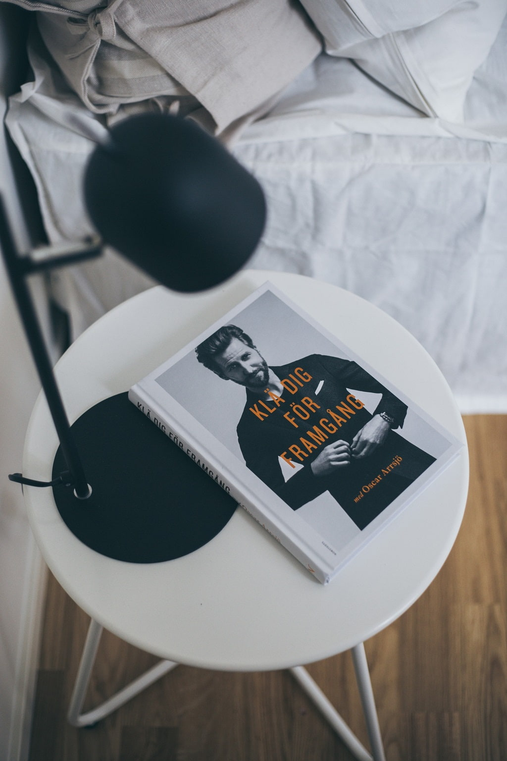 Närbild på sängbord med svart lampa och ett magasin