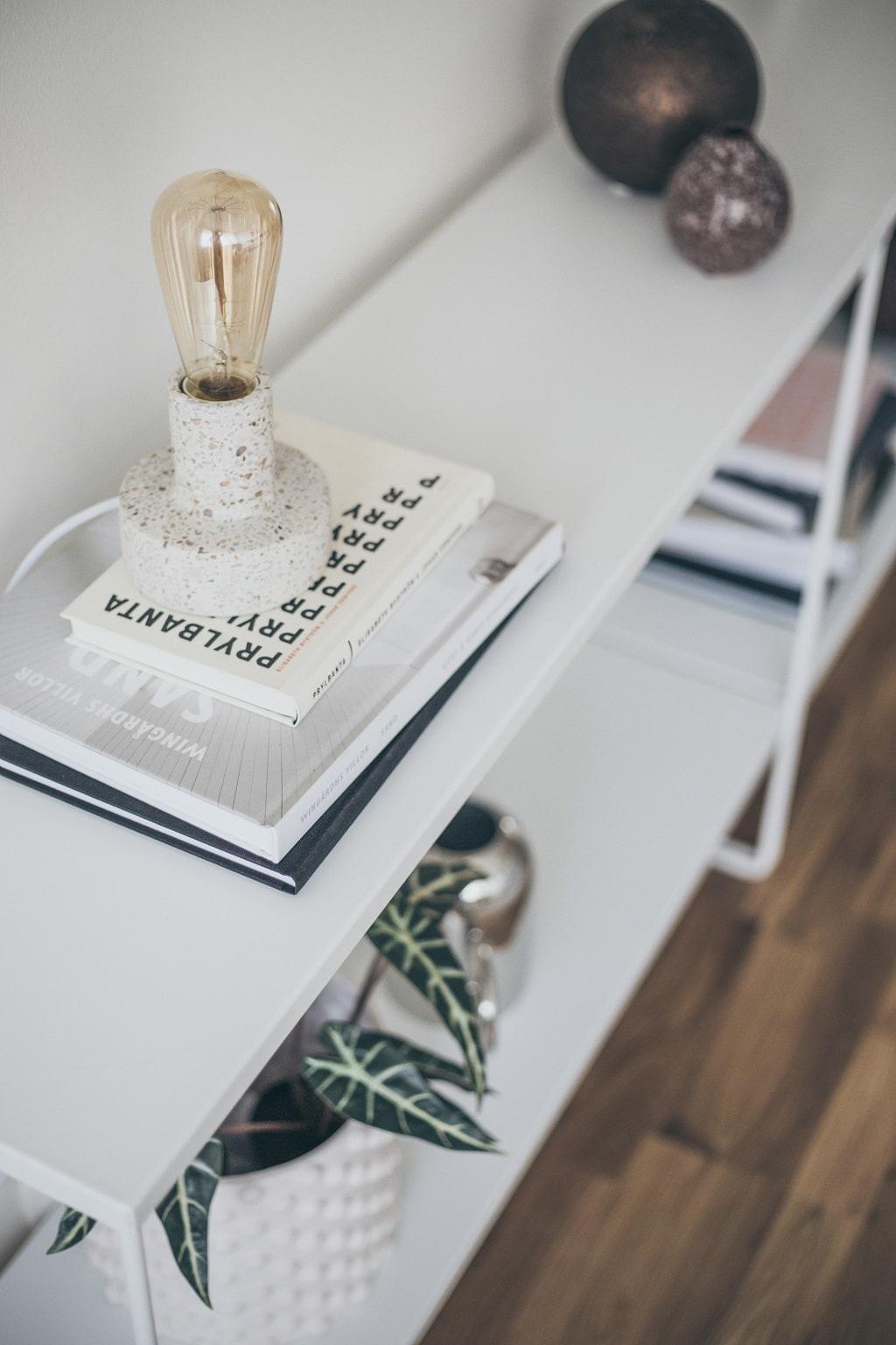 Närbild på sidobord med magasin, vaser och en lampa