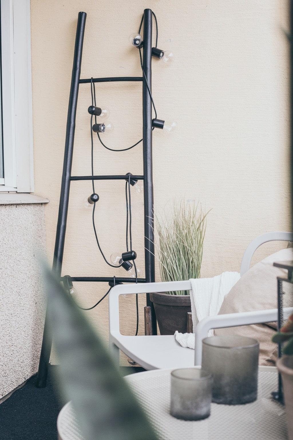 Uteplats med en stege lutad mot väggen med en ljusslinga på