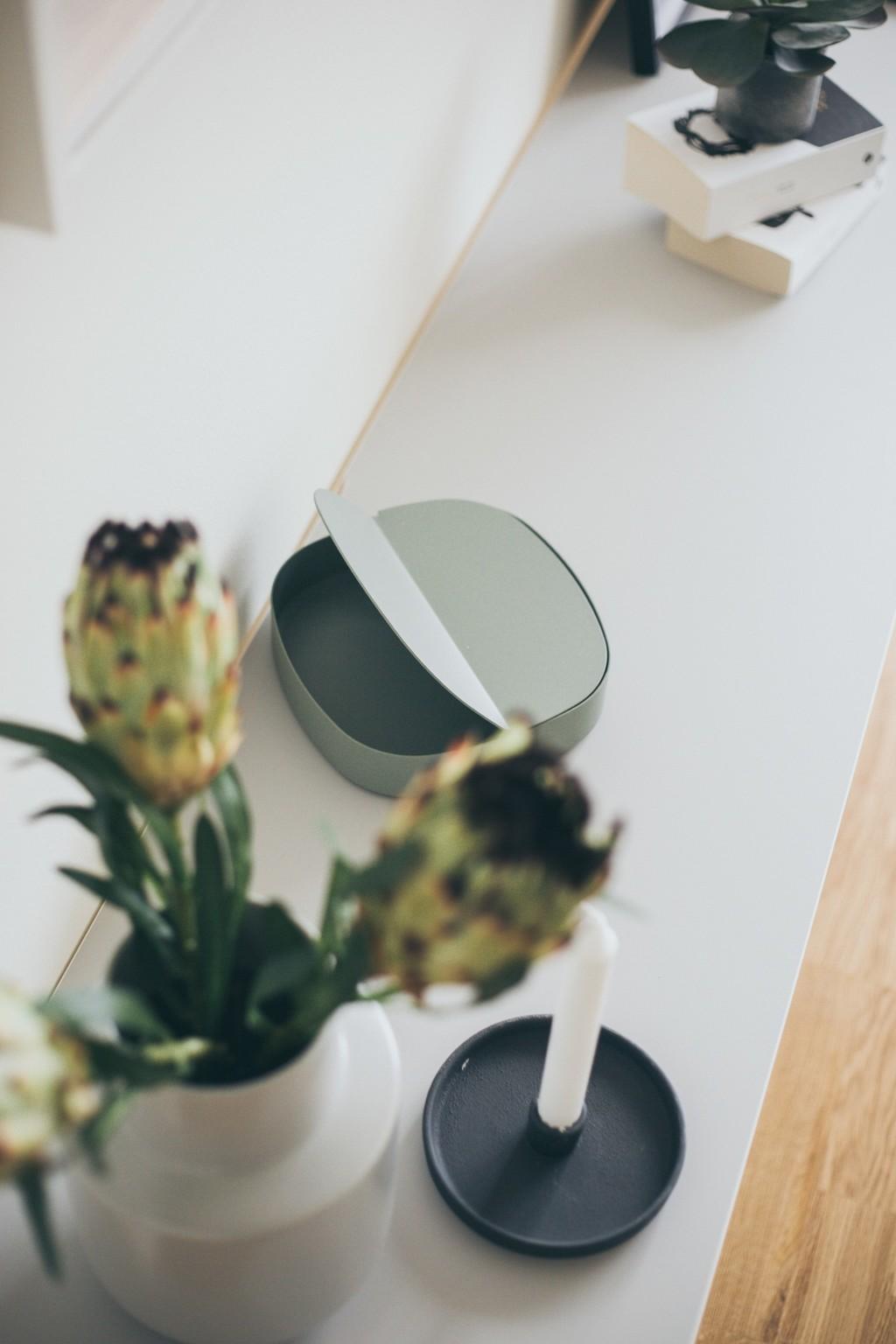 sidobord med vit vas och en grön ask