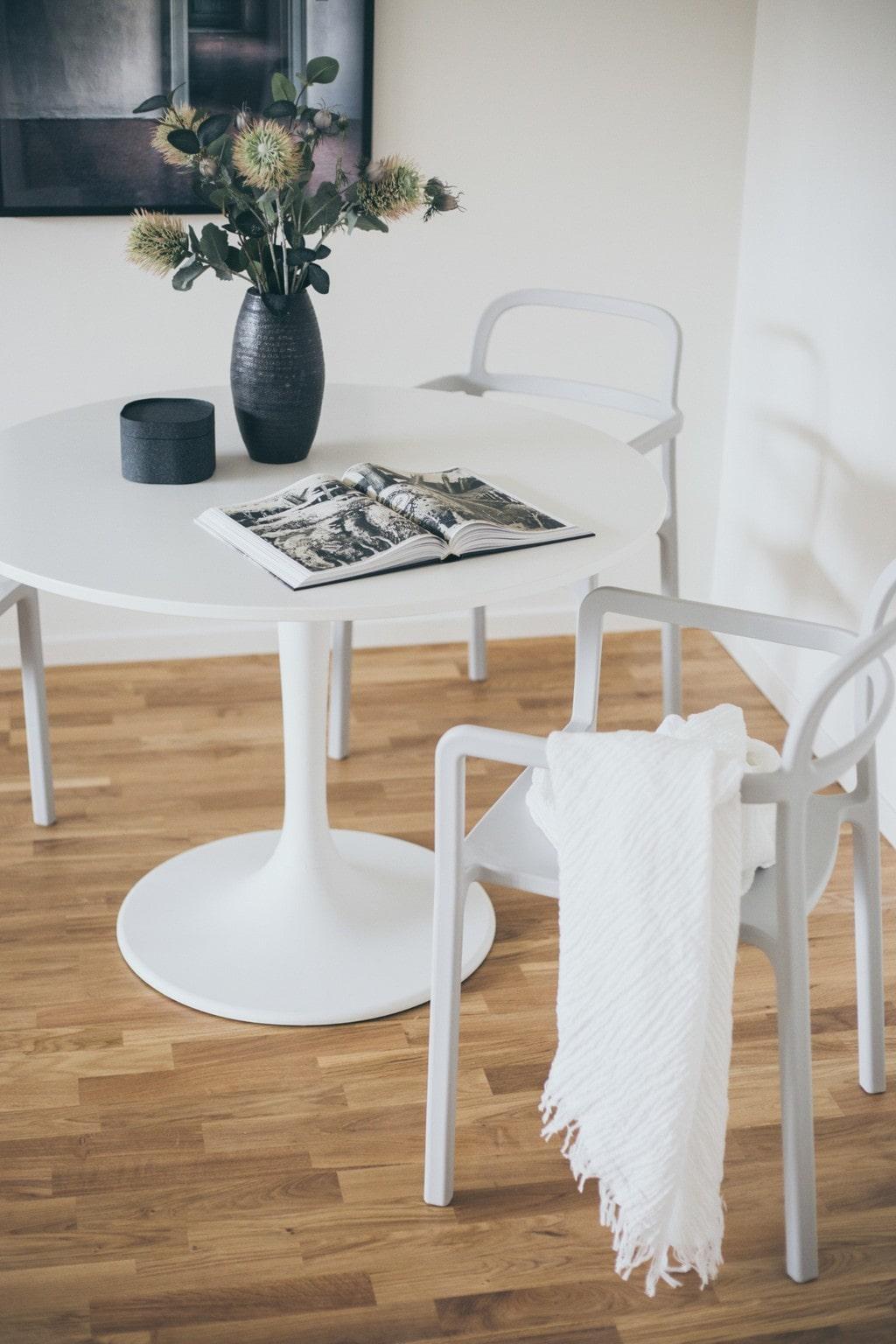 vitt runt pelarbord med vita stolar