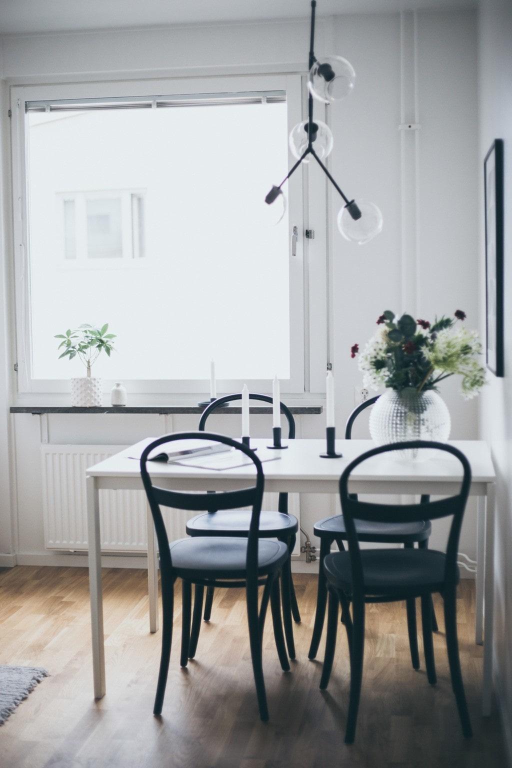 vitt köksbord med svarta stolar, svarta ljusstakar och taklampa