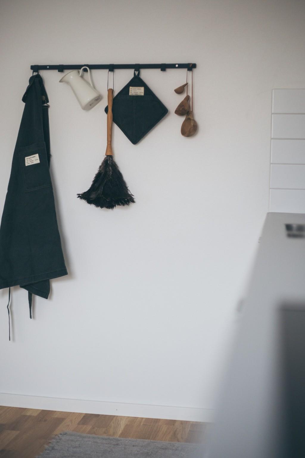 svarta krokar med förkläde, en kanna, en dammvippa, mått och grytlapp