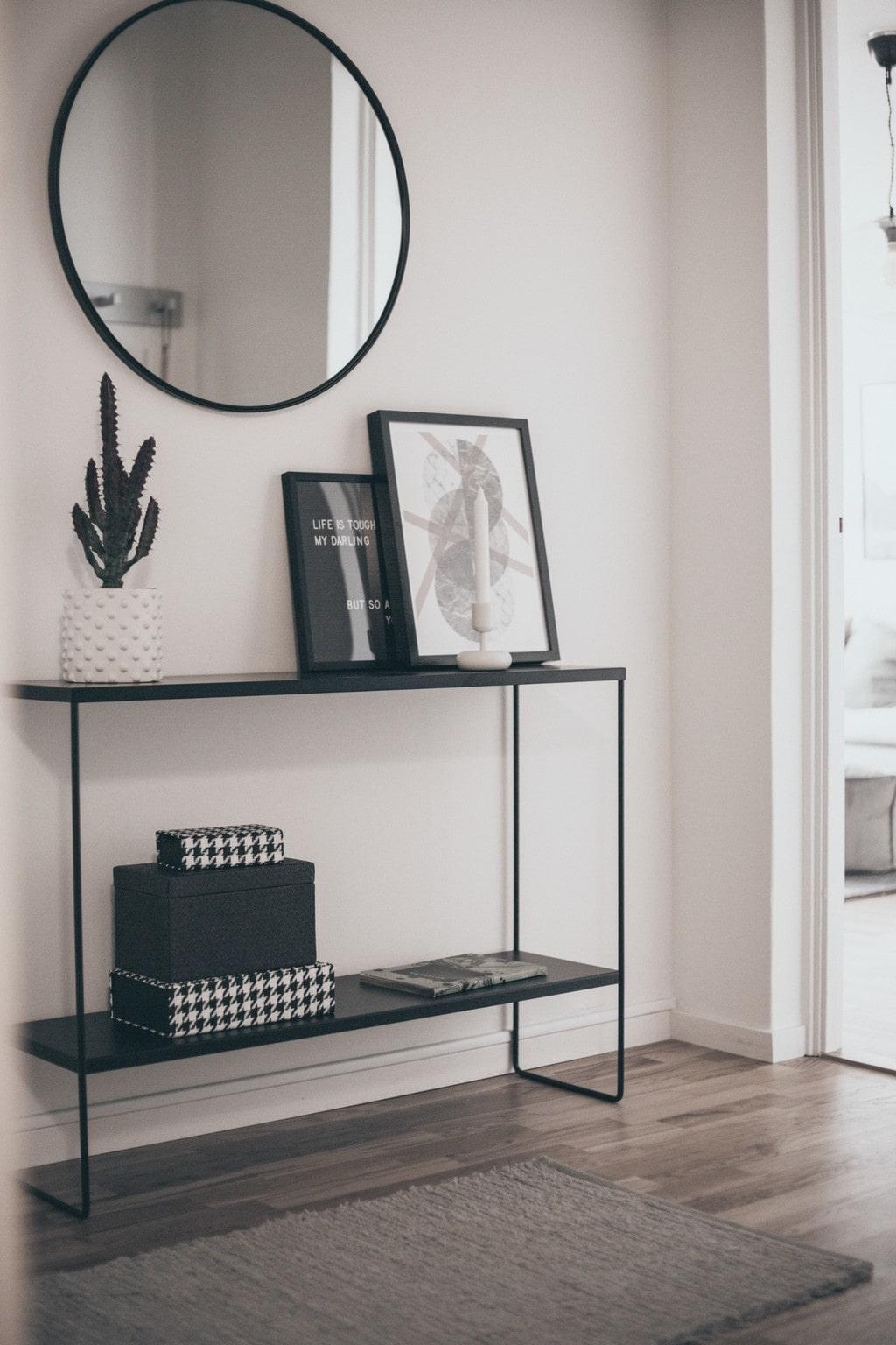 svart sideboard med en rund spegel ovanför