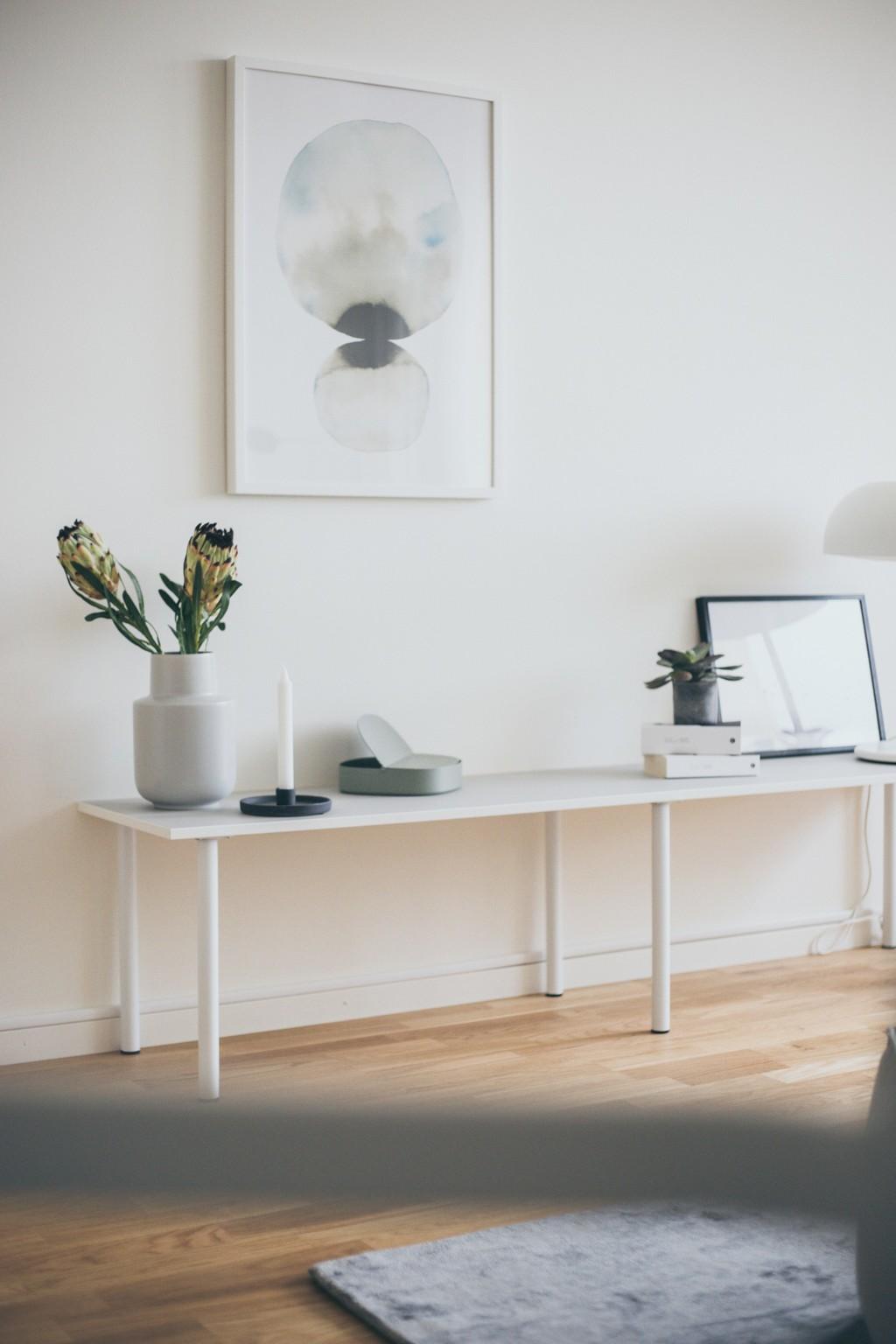 vitt sidobord med vit vas, stearinljus, ljusgrön ask, två böcker och en mindre växt