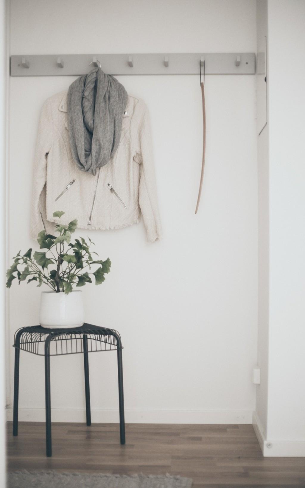ljusgrå kroklist med skoho och jacka, svart pall med en vit kruka
