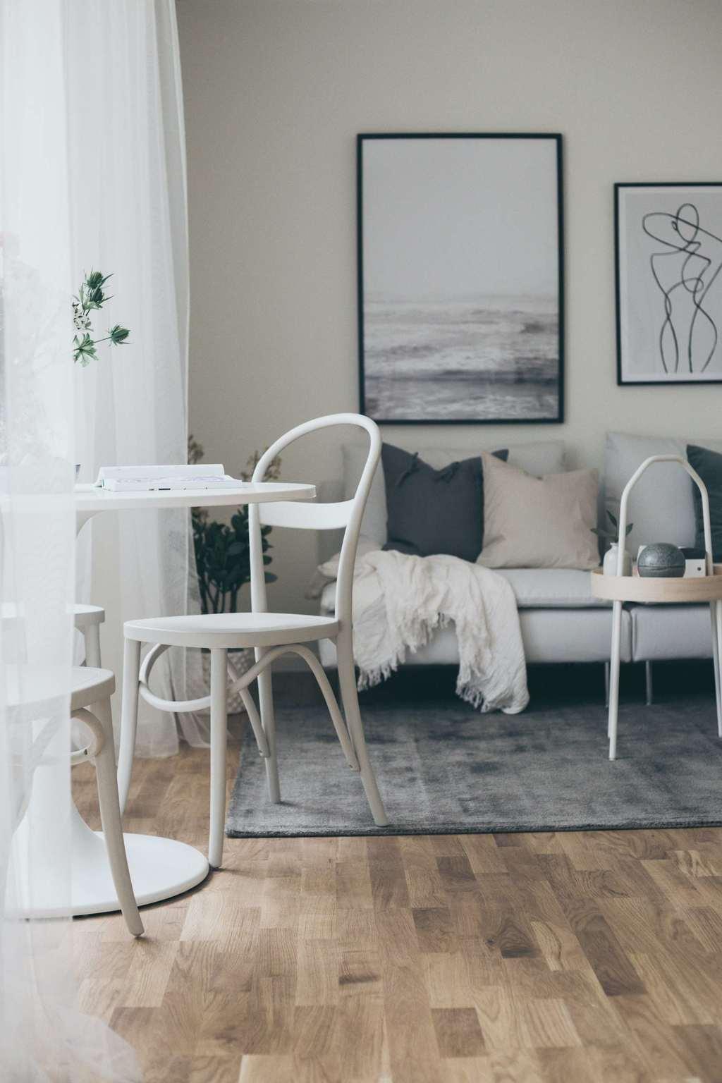vardagsrum med vitt pelarbord och en ljus soffa med beiga och grå kuddar